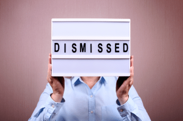 A man holding up a lightbox with the word 'dismissed' on