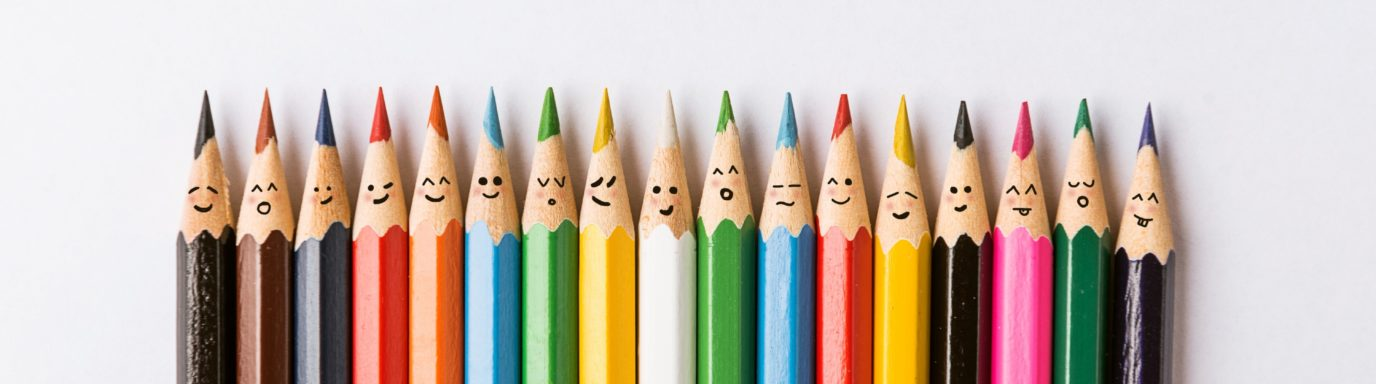 A row of different coloured pencils with faces